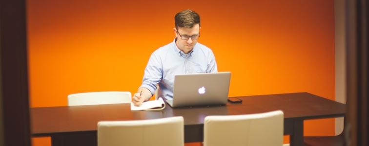 Человек работает в офисе с ноутбуком